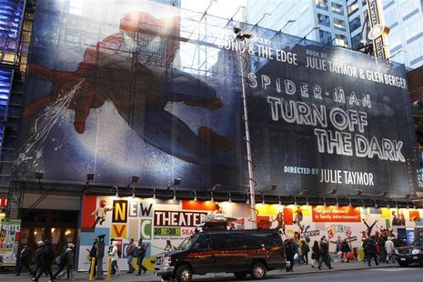 "Pedestrians walk underneath a banner advertising the Broadway play ""Spiderman: Turn Off The Dark"" in New York"