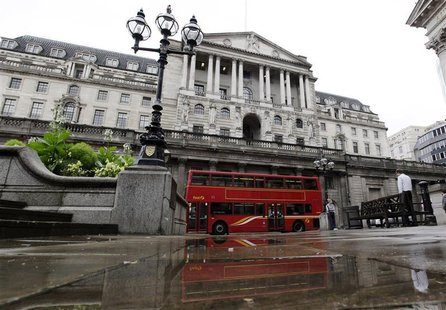 A double decker bus is reflected in a puddle after a rain shower outside the Bank of England in the City of London
