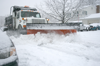A truck plows a snowy road in a stock image.