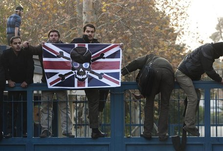 Iranian protesters climb over the gate of the British embassy in Tehran.