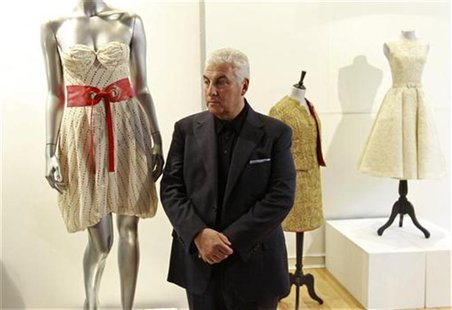 "Mitch Winehouse, the father of deceased British singer Amy Winehouse, poses for photographers next to the ""Back to Black"" album-cover dress"