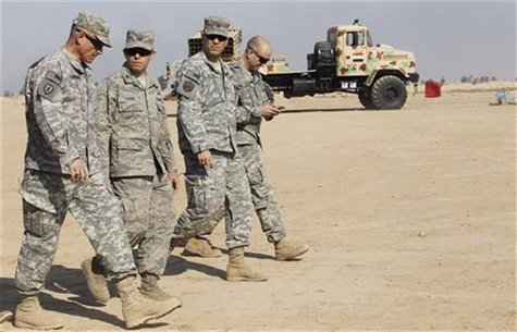 U.S. soldiers walk near a rocket launcher missile at Basmaya military base in Baghdad