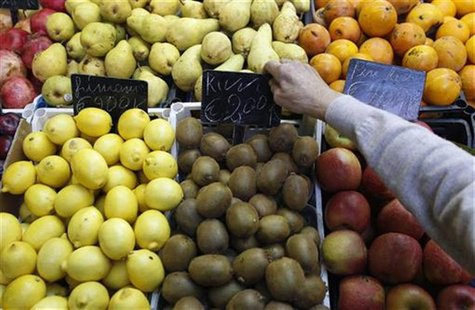 A fruit seller adjusts a price tag in a market in downtown Rome
