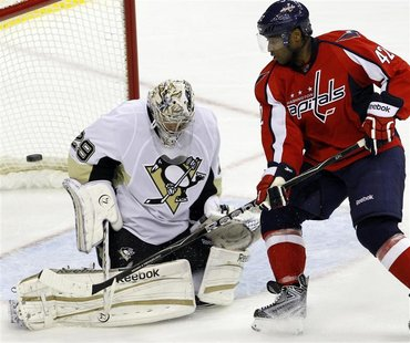 Pittsburgh Penguins Marc-Andre Fleury deflects a shot by Washington Capitals Joel Ward during their NHL hockey game in Washington