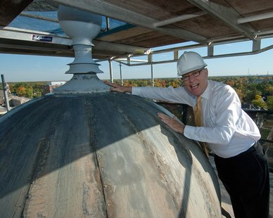 UWSP chancellor Bernie Patterson touches the top of the cupola. (Photo courtesy UWSP)
