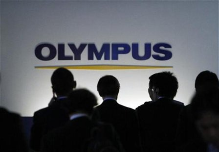 People walk past a sign of Olympus Corp outside the company's showroom in Tokyo