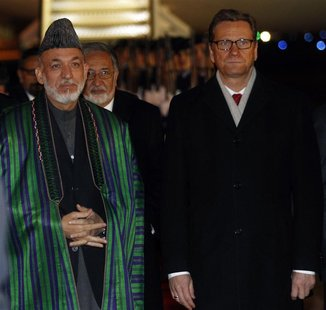 Afghan President Hamid Karzai is welcomed by German Foreign Minister Guido Westerwelle at the Cologne/Bonn military airport
