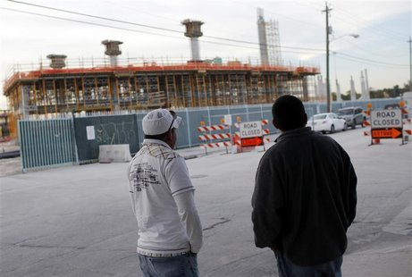 Workers wait outside the construction site of the new Florida Marlins stadium in downtown Miami, Florida