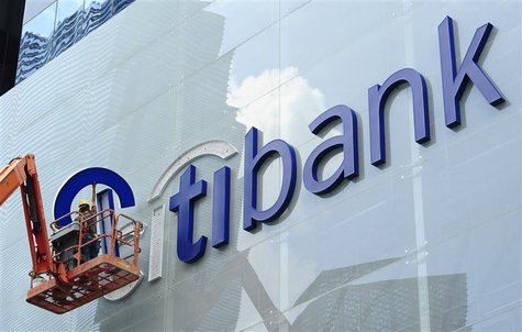 Construction workers install Citibank's neon sign on its Singapore main office at the central business district November 29, 2011.