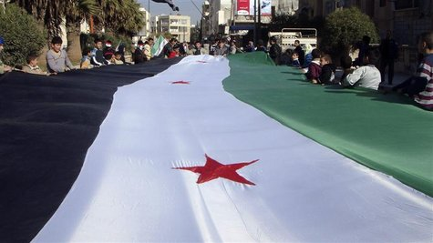 Demonstrators protesting against Syria's President Bashar al-Assad display a 1961-63 Syrian flag during a march through the streets in Adlb.