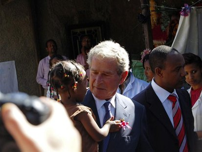 Former President Bush carries Ethiopian child whose mother is receiving HIV treatment through programmes funded by PEPFAR in Addis Ababa