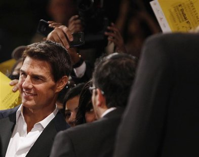 U.S. actor Cruise poses with fans as he arrives for the 8th Dubai International Film Festival