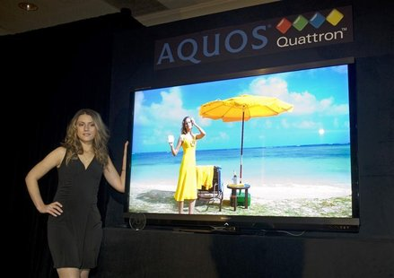 A model stands by a Sharp Quattron 70-inch LCD TV during a news conference at the 2011 International CES in Las Vegas