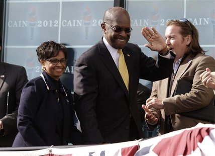 "Herman Cain arrives with his wife Gloria at his side to announce that he is ""suspending"" his presidential campaign in Atlanta"