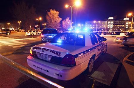 Law enforcement officers are seen at the site where a Virginia Tech police officer was shot and killed at Virginia Tech University Blacksburg, Virginia December 8, 2011. 