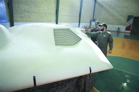 Undated picture shows member of Iran's revolutionary guard pointing at U.S. RQ-170 unmanned spy plane as he speaks with Hajizadeh at unknown