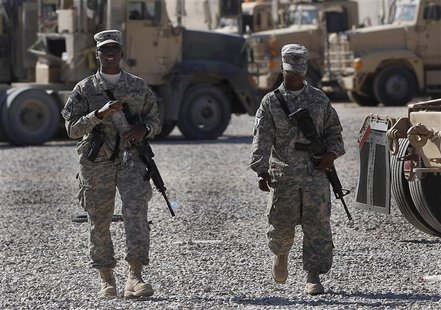 U.S. Army soldiers walk through a vehicle transport area inside Camp Adder, near Nasiriyah, Iraq