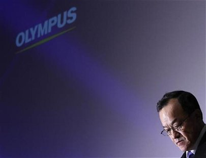 Olympus Corp's President Shuichi Takayama stands in front of its logo at the end of a news conference in Tokyo