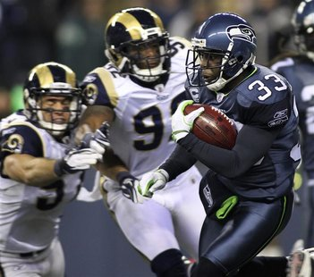 Seahawks' Washington runs for a kickoff return while avoiding being tackled by Rams Chamberlain and Sims during the second quarter of their