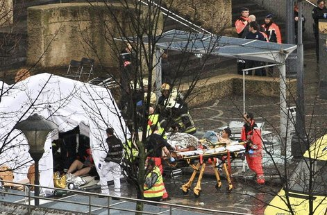 Rescuers evacuate injured people at the Place Saint Lambert square where two men threw explosives in the city center of the Belgian city of