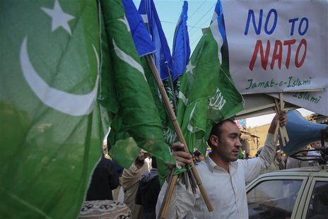A supporter of Jamaat-e-Islami (JI), a religious and political party, holds collected party flags and placards after an anti-American demons