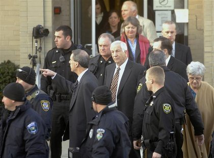 Former Penn State assistant football coach Sandusky is surrounded by police as he departs from a preliminary hearing in Bellefonte