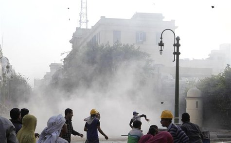 Protesters throw stones at army soldiers at a building next to cabinet offices near Tahrir Square in Cairo