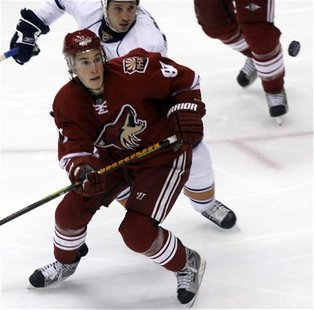 Phoenix Coyotes' Kyle Turris Edmonton Oilers' Fernando Pisani watch the puck as it flies in the air during the first period of their NHL hoc