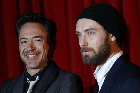 "U.S. actor Downey Jr. and British actor Law pose for photographers at the premiere of ""Sherlock Holmes: A Game of Shadows"" at the Empire Cin"