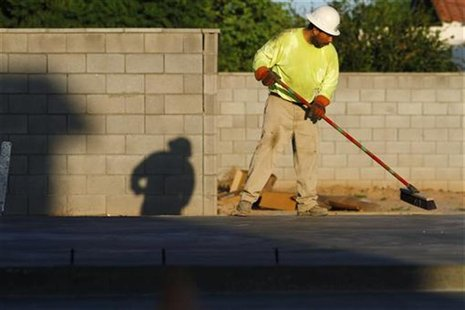 A worker sweeps the foundation of a house being constructed in Phoenix