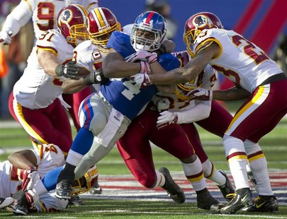 New York Giants Ahmad Bradshaw is stopped by Washington Redskins Ryan Kerrigan, London Fletcher and Oshiomogho Atogwe in NFL game in East Ru