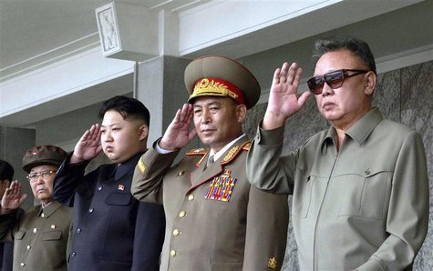 North Korean leader Kim Jong-il and his son Kim Jong Un salute as they watch soldiers attending a military parade in the Kim Il Sung square
