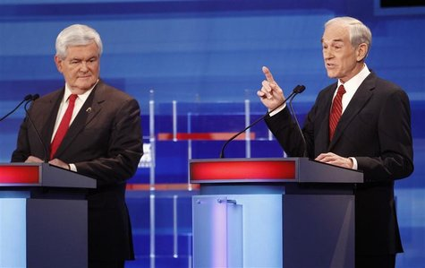 Republican presidential candidate Ron Paul makes a point as Newt Gingrich listens during the Republican Party presidential candidates debate