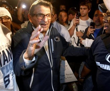Penn State University football coach Paterno walks to his residence after speaking to a group of students rallying outside it in State Colle