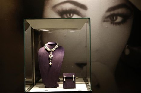 A photograph of Elizabeth Taylor is seen behind jewels on display as part of the upcoming auction at Christie's Auction house in New York