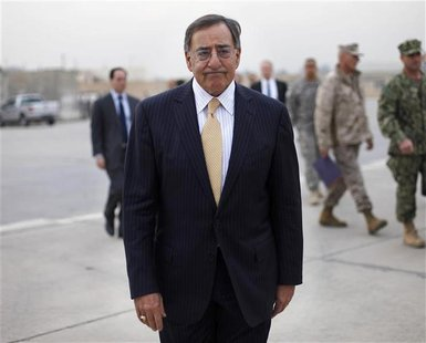 U.S. Secretary of Defense Leon Panetta walks across the tarmac towards his C-17 plane during his departure from Baghdad