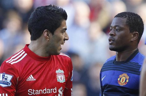 File photo of Liverpool's Suarez and Manchester United's Evra looking at each other during their English Premier League soccer match at Anfi