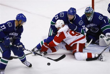Detroit Red Wings' Holmstrom fights for the puck against Vancouver Canucks' Edler in front of Canucks goaltender Luongo during the third per
