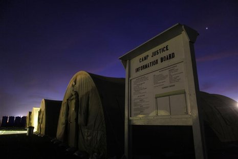 An information board stands posted near a row of tented sleeping quarters before dawn at Camp Justice at Guantanamo Bay Cuba