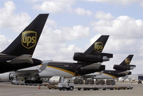 UPS employees load containers onto aircraft at World Port air hub during visit by U.S. Treasury Secretary Geithner in Louisville