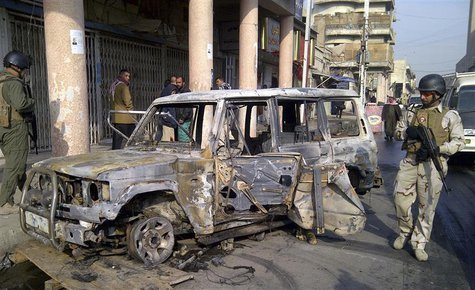 A soldier stands guard near a burnt vehicle after a bomb attack in Alawi district in central Baghdad