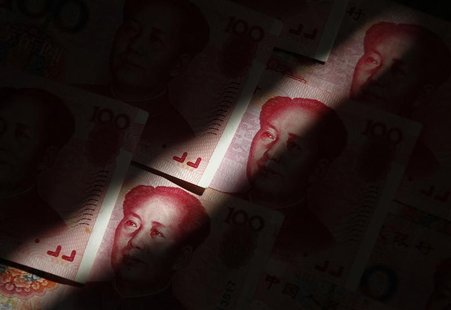 File photo of beam of light falling on Chinese 100 yuan banknotes in this photo illustration taken in Beijing