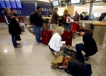 Holiday travelers check their bags at a Delta counter at Hartsfield-Jackson International Airport