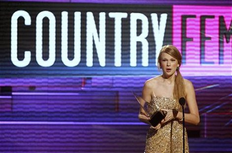 Singer Taylor Swift accepts the award for Favorite Female Country Artist at the 2011 American Music Awards in Los Angeles