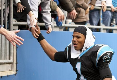 Carolina Panthers quarterback Cam Newton shakes hands with fans after playing the Tampa Bay Buccaneers during an NFL football game in Charlo