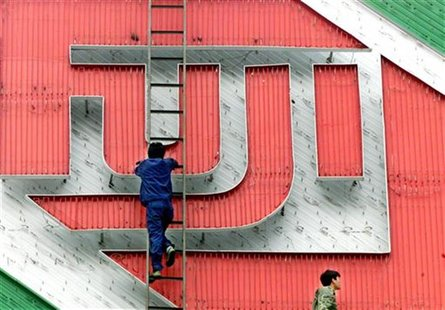 CHINESE WORKER REPAIRS FUJIFILM'S ADVERTISEMENT NEON BOARD IN BEIJING.