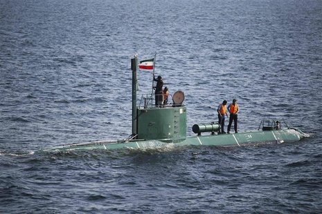 Military personnel place a flag on a submarine during the Velayat-90 war games by the Iranian navy in the Strait of Hormuz in southern Iran