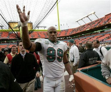 Miami Dolphins linebacker Jason Taylor waves as he leaves the field in Miami