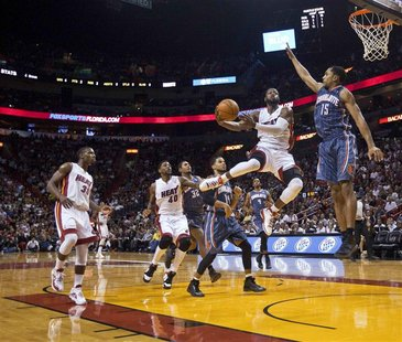 Heat's Wade dives as Bobcats' Henderson defends in their NBA basketball game in Miami