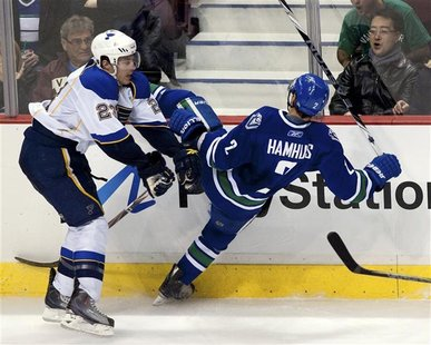 St. Louis Blues Ian Cole lays a hit on Dan Hamhuis of the Vancouver Canucks during their NHL hockey game in Vancouver.